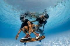 Faire de la planche à roulettes sous l'eau Photo stock