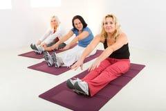 faire des femmes de couvre-tapis d'exercices photographie stock libre de droits