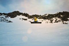 Faire du surf des neiges au coucher du soleil en montagnes photos libres de droits