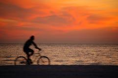 Faire du vélo au coucher du soleil Images libres de droits