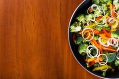 Faire frire des légumes dans la casserole avec le fond en bois Photo libre de droits