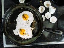 Faire frire des oeufs dans une casserole de fonte Photo stock