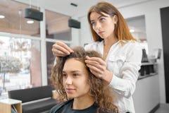 Faire la nouvelle coiffure dans le salon beaty avec le hairstyler professionnel image libre de droits