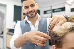 Faire la nouvelle coiffure pour le modèle masculin utilisant des ciseaux métalliques pointus photographie stock