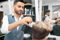 Faire la nouvelle coiffure pour le modèle masculin utilisant la laque photo stock