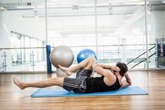Faire musculaire d'homme abdominal sur le tapis Image libre de droits
