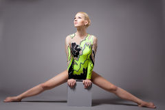 Faire professionnel mignon de gymnaste fractionnements sur le cube photos stock