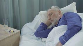 Faire une sieste patient masculin dans la salle d'hôpital, voir des rêves et parler dans le sommeil banque de vidéos