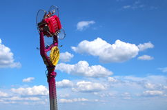 Fairground attraction in the sky. Fairground attraction with people high in the sky with clouds Stock Photos