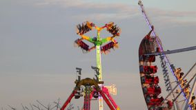 Fairground attractions at sunset (04). Fairground attractions by rotating at sunset with large colorful of neon lights and motion stock video