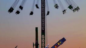 Fairground attractions at sunset. Fairground attractions by rotating at sunset with large colorful of neon lights and motion stock video