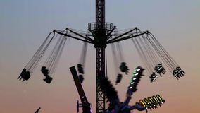 Fairground attractions at sunset (07). Fairground attractions by rotating at sunset with large colorful of neon lights and motion.Time Lapse stock video