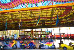 Fairground bumper car for little childrens. Dodgems motorcycle aligned and rows on the corner of the electrical circuit trace and waiting customers. Shooting stock photos