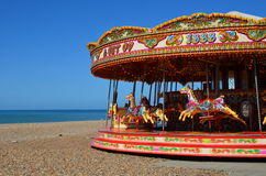 Fairground carousel on Brighton beach. Traditional fairground merry go round on the seafront at Brighton, East Sussex in the United Kingdom Royalty Free Stock Photo