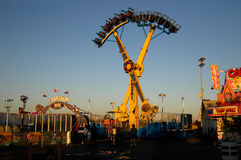 Fairground at dusk. A fairground scene with a candy apple vendor, fair ride, and people at dusk royalty free stock photography