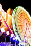 Fairground at Night. Night time motion blur with spinning ferris wheel Royalty Free Stock Photo