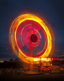 Fairground ride at night. Long exposure of a fairground ride causing light trails Stock Image
