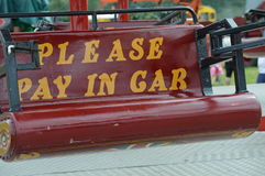 Fairground ride sign. Please pay in car sign painted on a fairground ride Royalty Free Stock Image