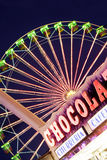 Fairground Scene. Ferris wheel with chocolate stand in the foreground Stock Photo