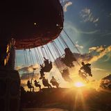 Fairground sunset. Swinging on a carousel ride as the sun sets on a summer evening Stock Images