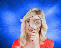 Fairhaired woman looking through a magnifying glass Stock Photo