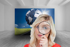 Fairhaired woman looking through a magnifying glass Royalty Free Stock Photo