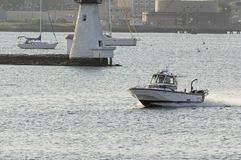 Fairhaven harbormaster patrol boat passing lighthouse stock images