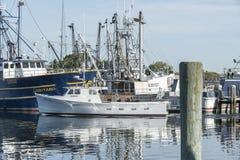 Commercial fishing vessel Miss Molly passing larger boat. Fairhaven, Massachusetts, USA - June 9, 2019: Lobster boat Miss Molly, hailing port Mattapoisett stock images