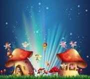 Fairies flying over mushroom houses Stock Images
