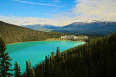 Fairmont Chateau Hotel Lake Louise. Fairmont Chateau Hotel Sits on the Aqua colored waters of Lake Louise in Banff Canada surrounded by green pine trees and snow royalty free stock photos