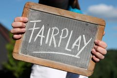 FAIRPLAY. Written with chalk on slate shown by young female Royalty Free Stock Photography