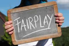 Fairplay. Written with chalk on writing slate shown by young female Royalty Free Stock Images