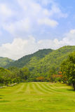 Fairway of a golf course beside the mountain. Golf fairway of a golf course, surrounded by bushes and trees, beside the mountain Stock Photo