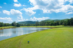 Fairway on green grass with cloudy blue sky and lake Royalty Free Stock Photo