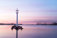 Fairway lighthouse at port channel in sunset hour. Stock Photo
