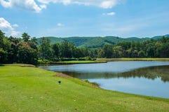 Fairway na grama verde com o céu azul e o lago nebulosos Fotografia de Stock