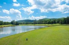 Fairway na grama verde com o céu azul e o lago nebulosos Foto de Stock Royalty Free