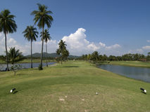 Fairway of par 4 golf hole. Tee-box and fairway of par 4 golf hole at tropical resort in Rayong province, Thailand. Water on both sides of the fairway Stock Images