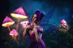 Fairy кокетка стоя около огромного гриба Стоковая Фотография