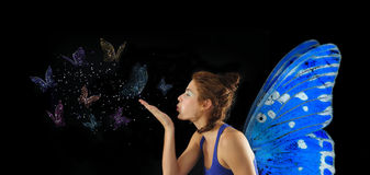 Fairy blowing butterflies. Fairy with blue wings blowing butterflies, isolated over black Royalty Free Stock Image