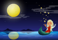 A fairy in a boat holding a wand Royalty Free Stock Photo
