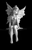 Fairy. A ceramic fairy figurine sitting in front of a black background royalty free stock photos