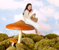 Fairy child on a toadstool. Little fairy child sitting on a toadstool eating an apple stock photography