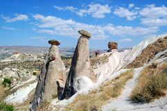 Fairy chimneys in Cappadocia. The interesting rock formations, known as fairy chimneys, have been formed as the result of the erosion of this tufa layer Stock Photos