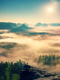 Fairy daybreak. Misty awakening in a beautiful hills. Peaks of hills are sticking out from foggy background Stock Photos