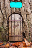 Fairy door 2. Fairy door in a tree trunk with autumn leaves on the ground in front of the entrance. With space for text. The little potting shed is closed, at Stock Image