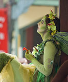 Fairy. A fantasy performer dressed and painted as a fairy sits in a window sill, holding a small flower stock photo