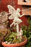 Fairy in a Flower Pot. White plastic fairy in a plant potter against a red brick wall Royalty Free Stock Photo