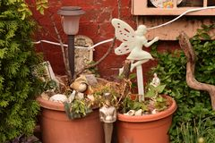 Fairy in a Flower Pot. White plastic fairy in a plant potter against a red brick wall Stock Photos