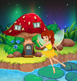 A fairy flying near the red mushroom house Stock Photo